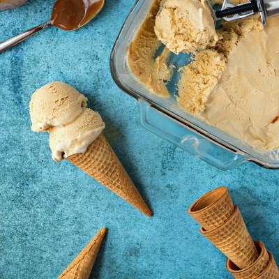 styled shot of of Salted Caramel Ice Cream in a glass dish with an ice cream scooper with sugar cones and a full ice cream cone next to it and a jar and spoon of caramel sauce