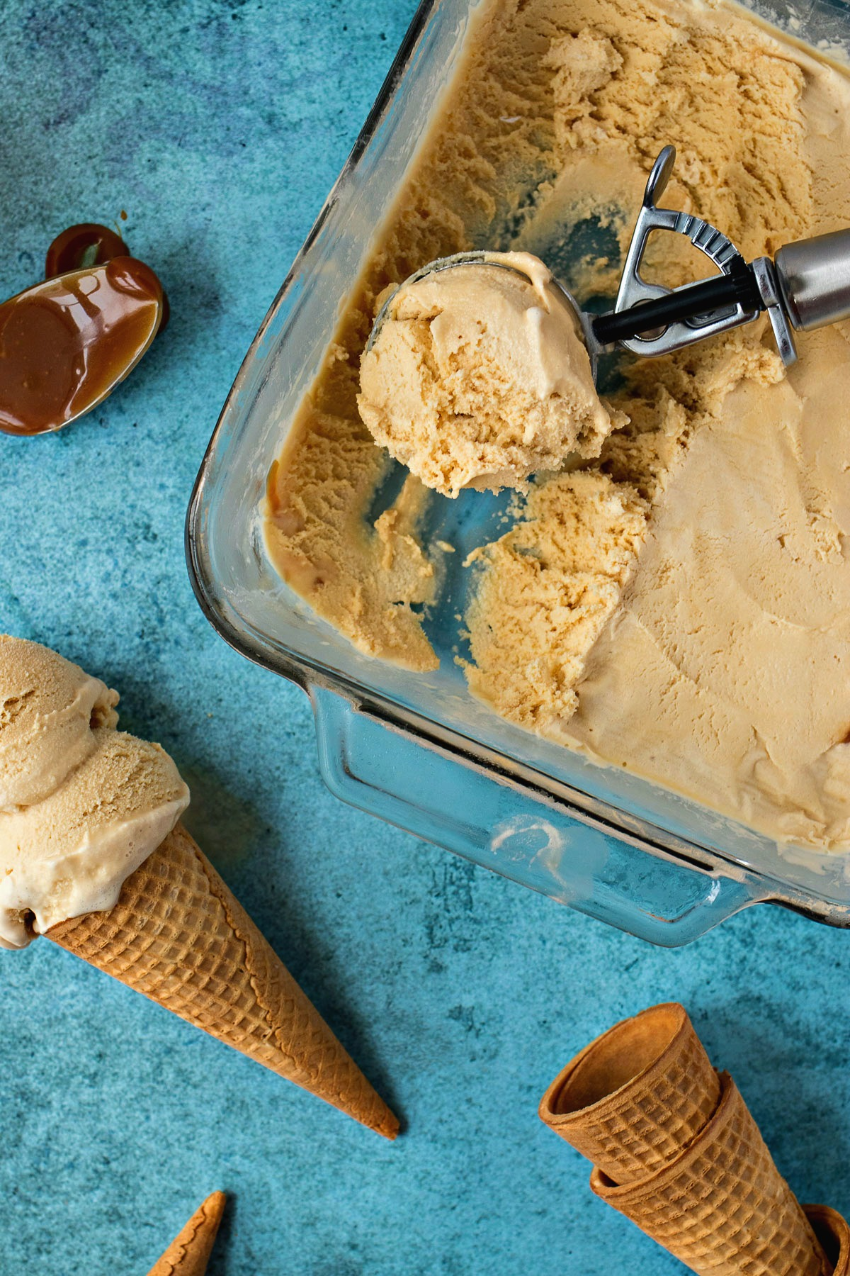 Cookie scoop scooping out Salted Caramel Ice Cream from a pan