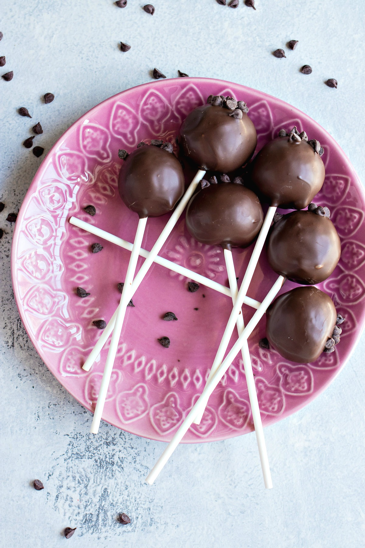 Chocolate Chip Cookie Cake Pops covered in melted chocolate and chocolate chips on a plate