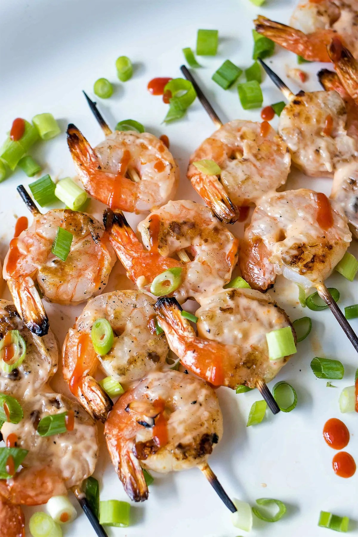 Grilled Bang Bang Shrimp Skewers covered in scallions and Bang Bang sauce