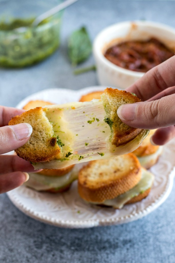 a Mini Pesto Grilled Cheese being pulled apart with stringy cheese with a plate of more sandwiches and bowls of pesto and dipping sauce in the background, shot from a side angle