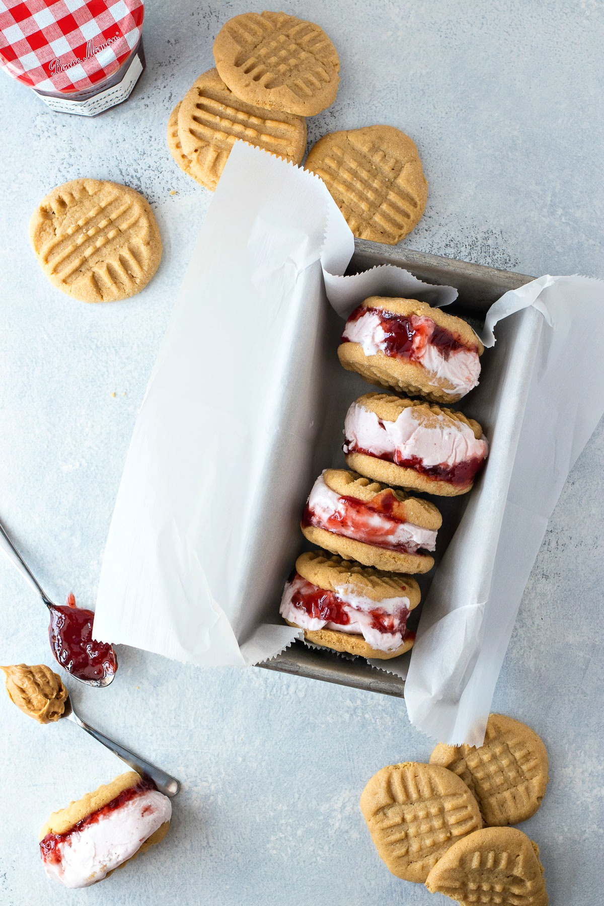 PB&J Ice Cream Sandwiches surrounded by peanut butter cookies and a jelly jar