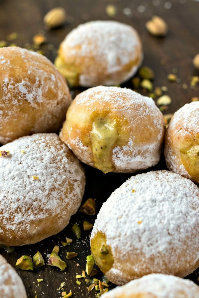 Pistachio Cream Doughnuts – Super fluffy yeast doughnuts are tossed in powdered sugar and filled with homemade pistachio pastry cream. These doughnuts are going to be your family's new favorite breakfast treat!