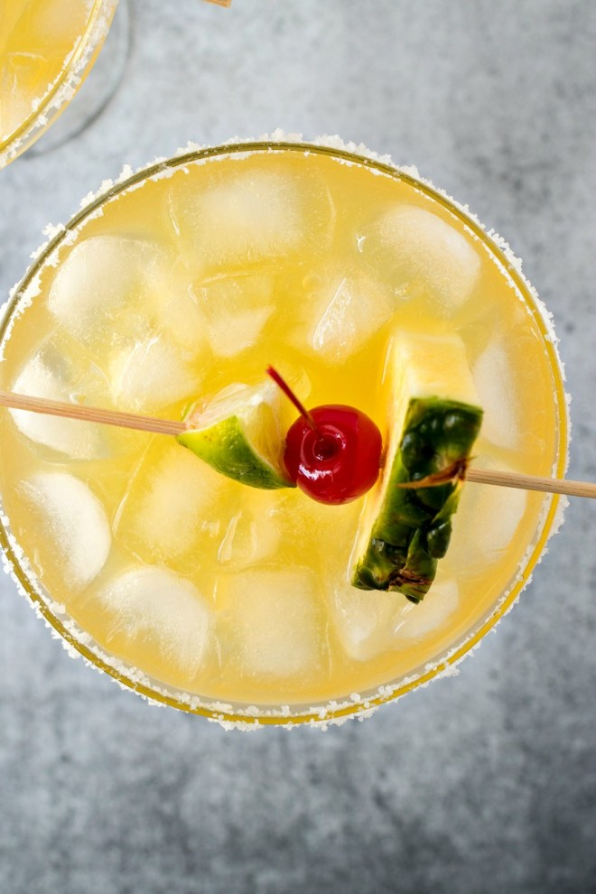 Tropical Red Bull Margaritas - A blend of pineapple, mango, and guava juices is combined with your typical margarita ingredients plus a boost from Red Bull Energy Drink to make these incredible Tropical Red Bull Margaritas.