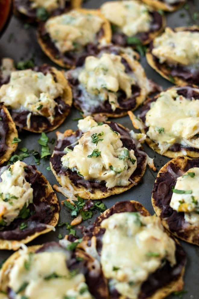Verde Chicken Tostada Bites - Round corn tortilla chips are topped with refried black beans, chopped chicken, creamy salsa verde sauce, and shredded Monterey Jack cheese