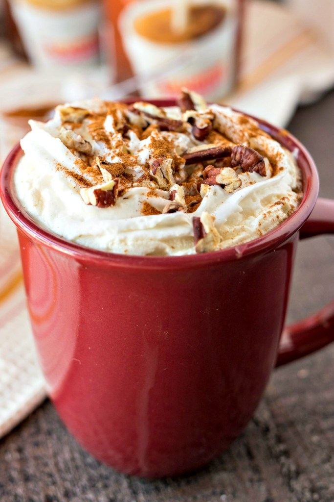 a mug of Cinnamon Maple Latte topped with whipped cream and chopped pecans with canisters of coffee creamer in the background, shot from a side angle