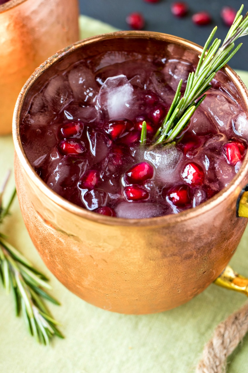 Closeup of a Pomegranate Rosemary Moscow Mule with pieces of pomegranate in the mug