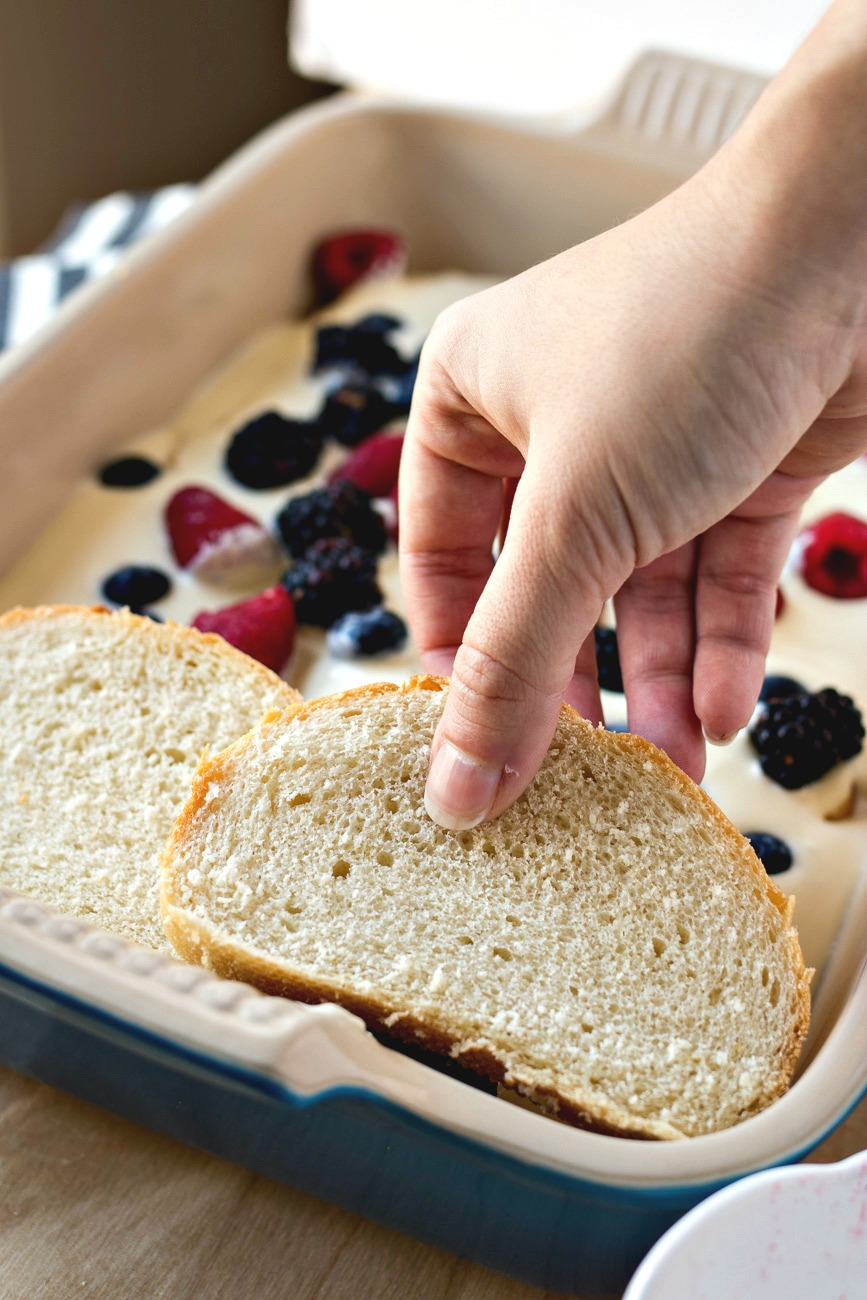Adding another layer of bread slices on top of the berries and cream cheese layer