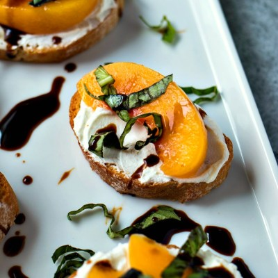 Peach & Goat Cheese Crostini - Slices of crusty, toasted baguette are rubbed with garlic, topped with whipped goat cheese and sliced peaches, and finished with basil and a drizzle of balsamic glaze. Perfectly paired with Notable Wines Fruity & Crisp Chardonnay.