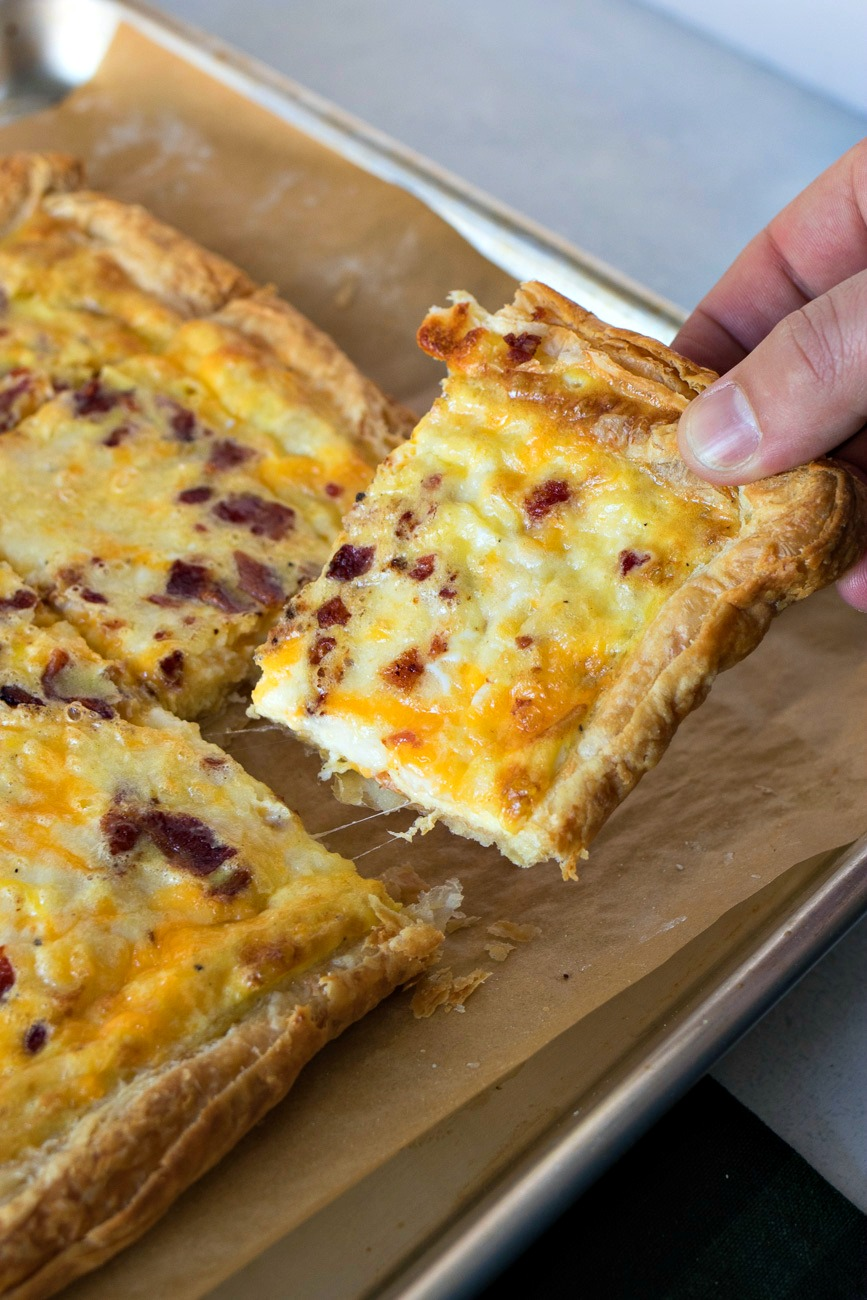 Breakfast Pizza - Crispy puff pastry is loaded with your breakfast favorites: eggs, two kinds of cheese, and bacon. It's the best thing to serve the whole family on the weekends or for a special brunch!