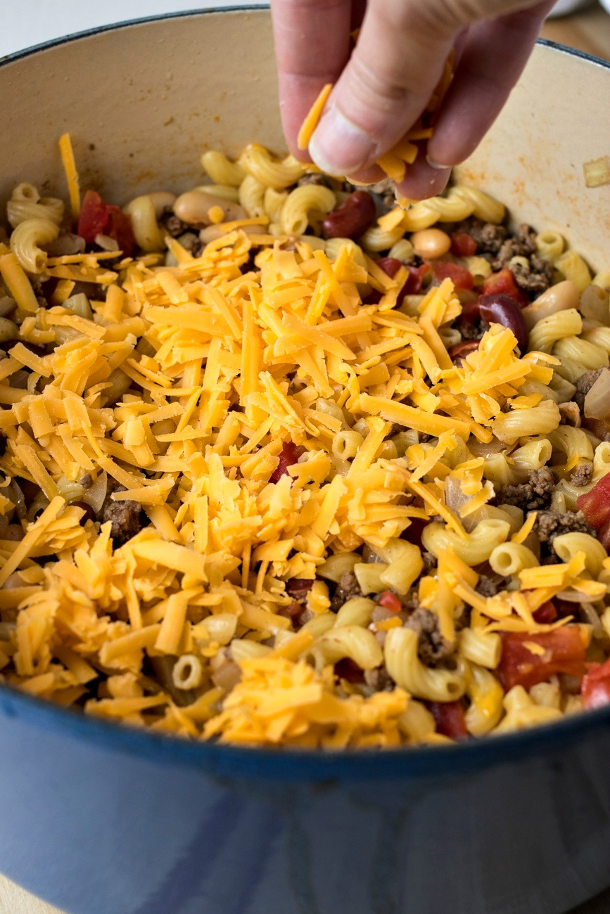 Adding cheese to the top of the Chili Mac & Cheese ingredients
