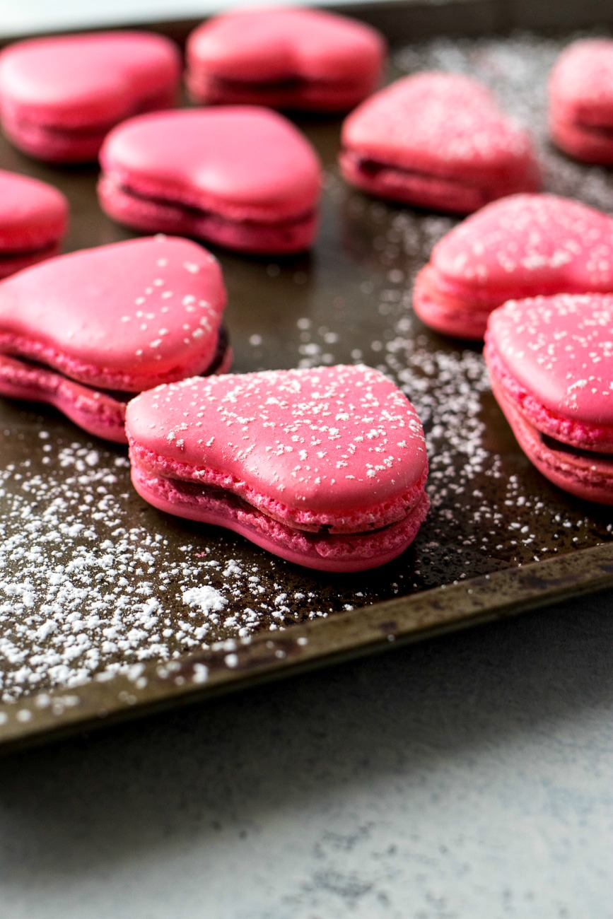 Cookie sheet of Raspberry Macaron Hearts covered in powdered sugar