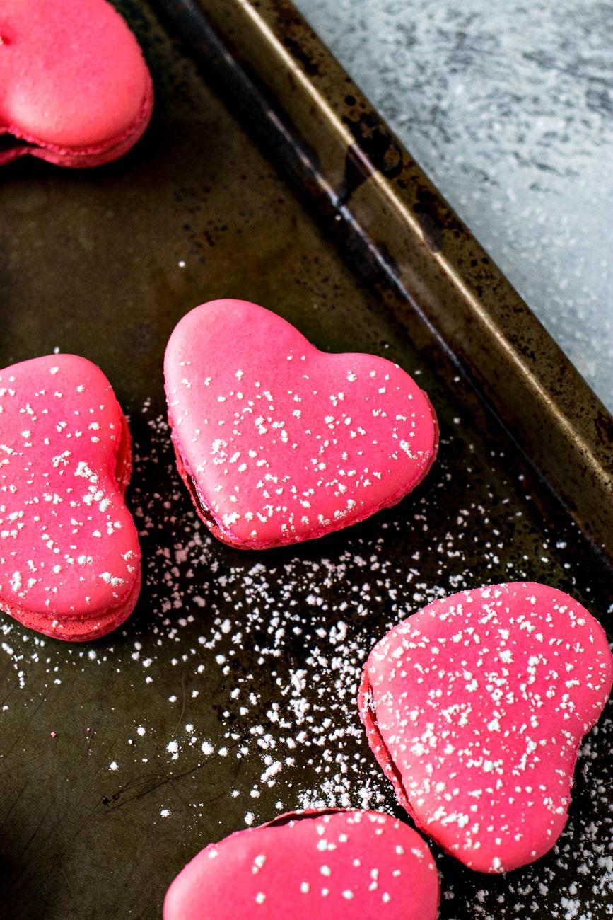 Raspberry Macaron Hearts on a cookie sheet