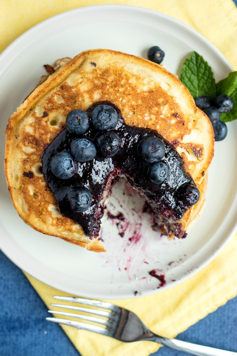 Lemon Blueberry Ricotta Pancakes with a wedge cut out