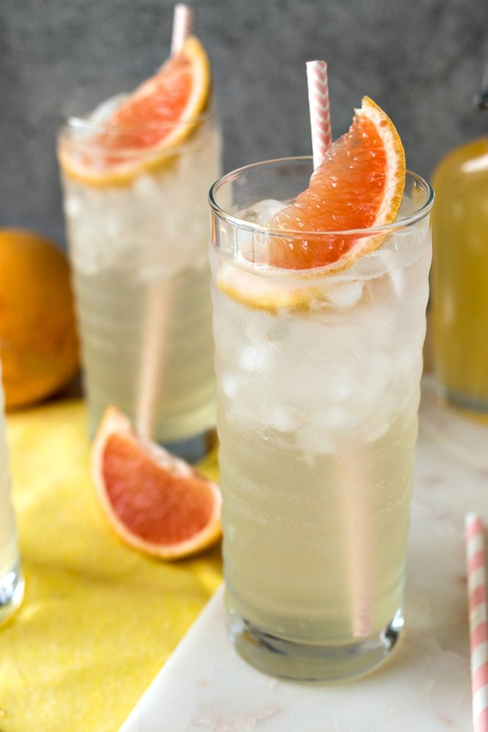 two glasses of Homemade Grapefruit Soda filled with ice and a piece of grapefruit and straw on a cloth napkin with grapefruit slices around the glasses, shot from a side angle