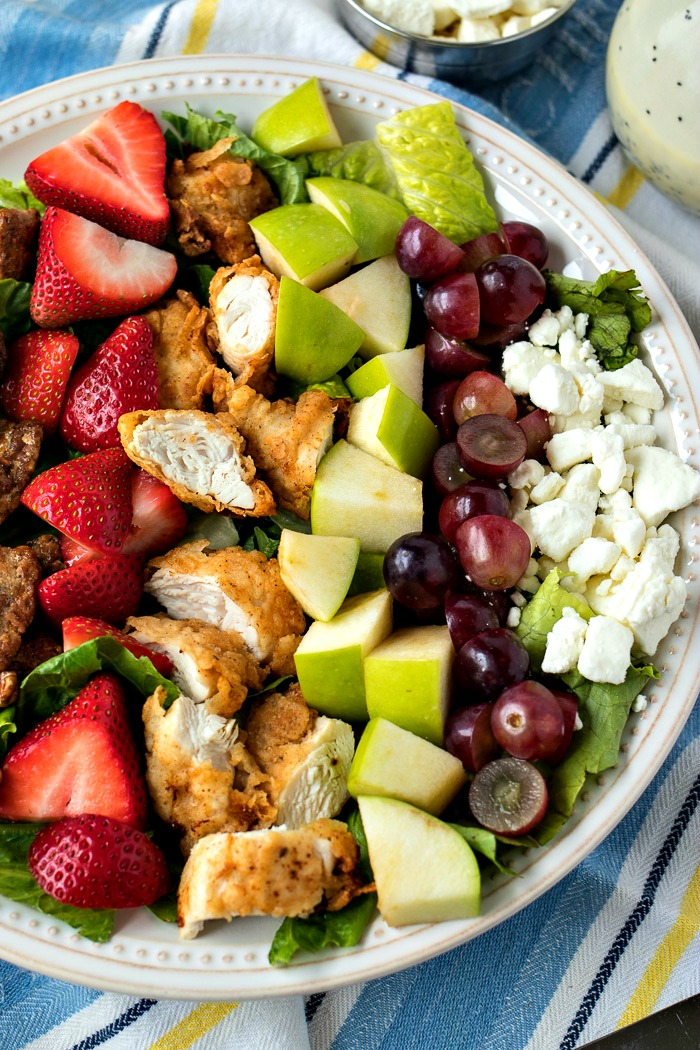 Southern Cobb Salad - A Southern take on a Cobb salad, loaded with fried chicken tenders, fresh strawberries, grapes, Granny Smith apples, candied pecans and crumbled goat cheese. Served with a homemade poppyseed dressing.