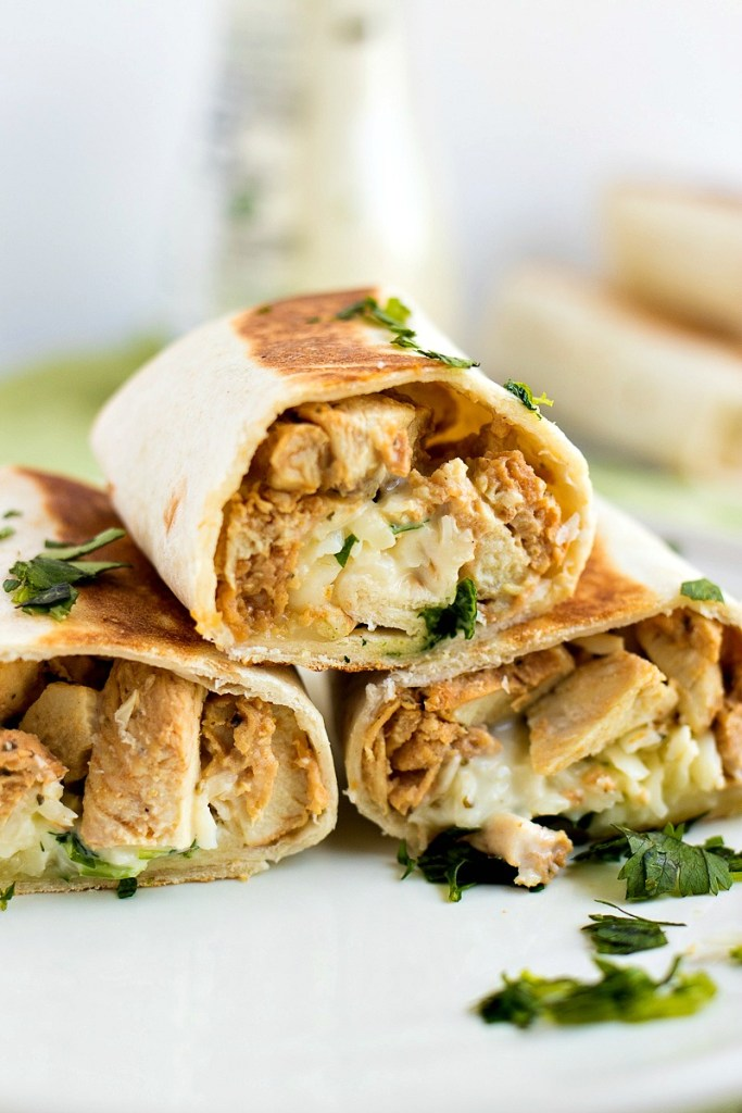 three Chicken Ranch Wraps stacked on top of each other on a plate and sprinkled with cilantro with a jar of ranch in the background, shot from the front