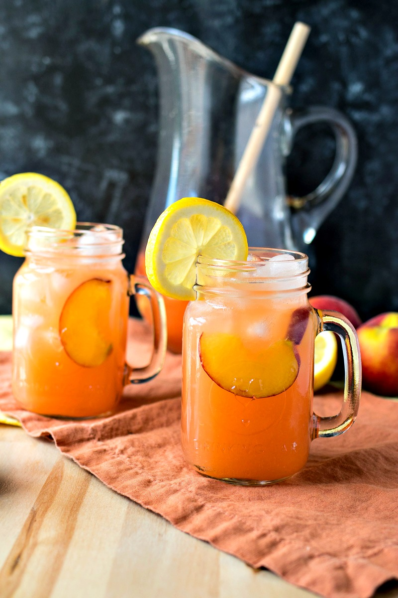 Two glasses of Peach Lemonade in front of a pitcher