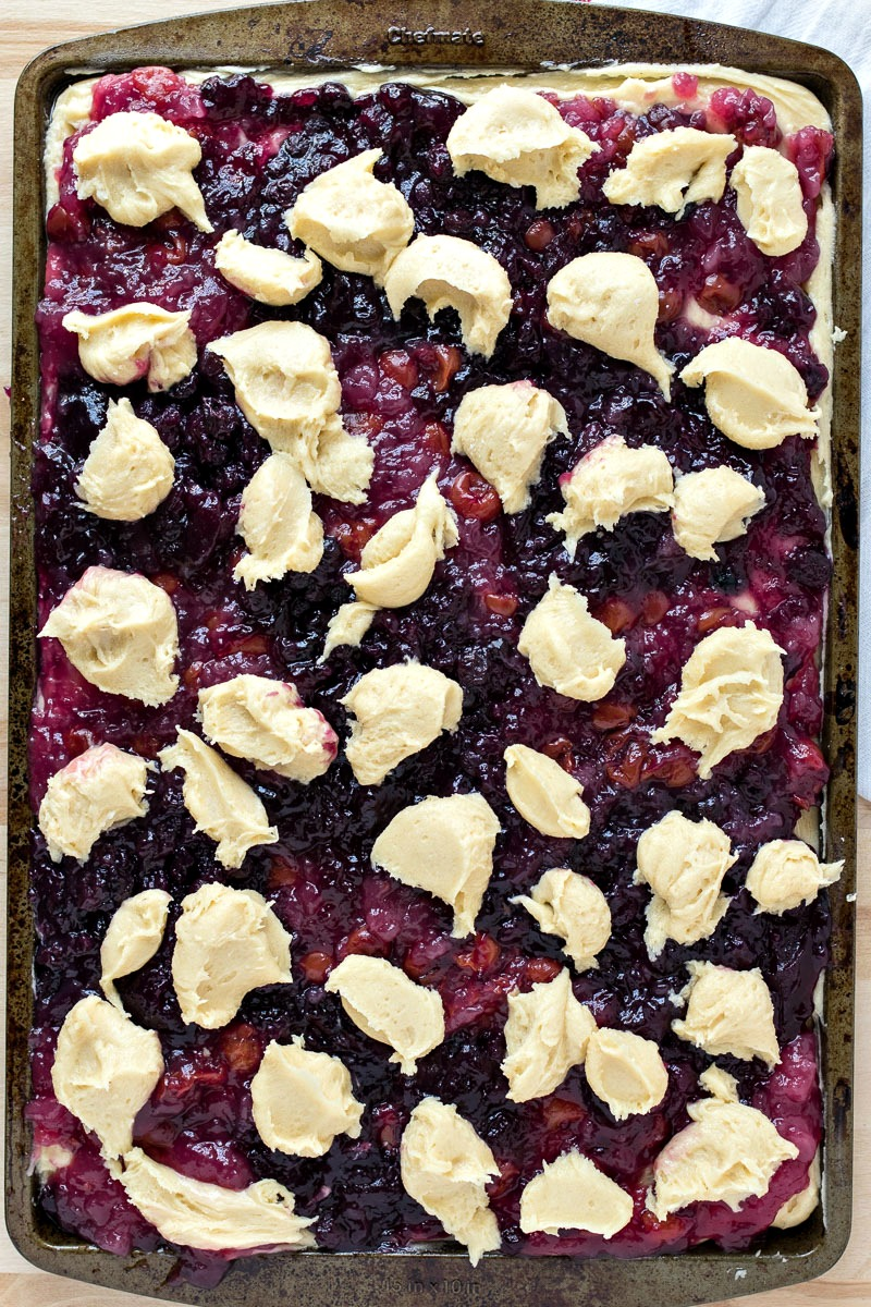Cherry and blueberry pie filling on top of the dough, with bits of dough scattered across the cookie sheet