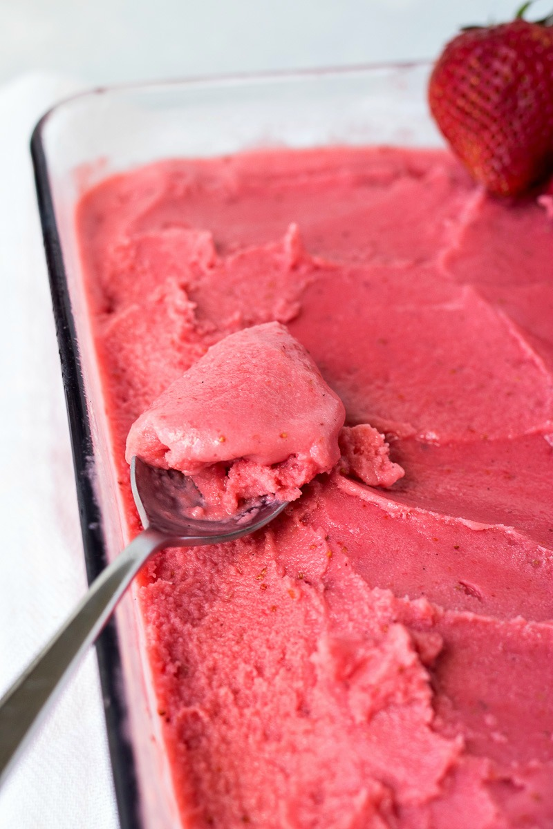 Spoon in a pan of Strawberry Coconut Sorbet