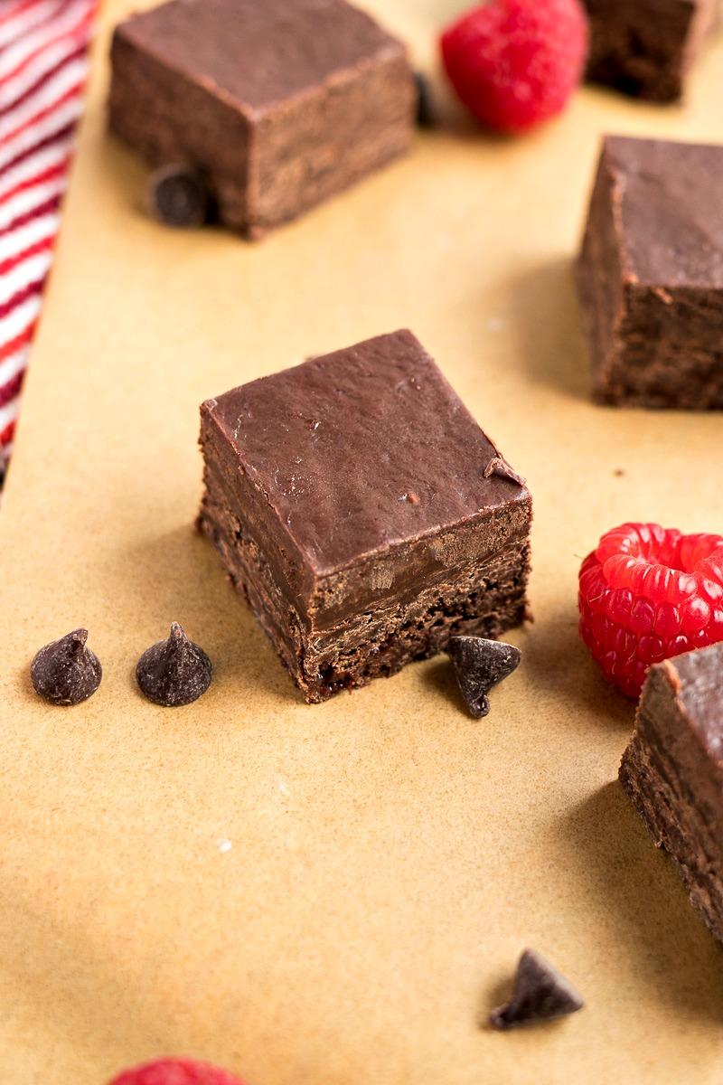 Dark Chocolate Raspberry Fudge squares with chocolate chips and raspberries around them