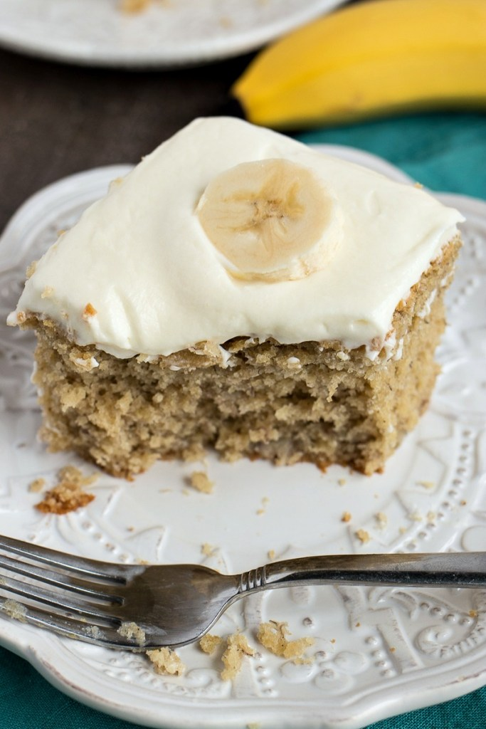 a plate of Easy Banana Cake with a bite out of it and a fork on it with another plate of cake and a banana and a cloth napkin underneath it, shot from a side angle