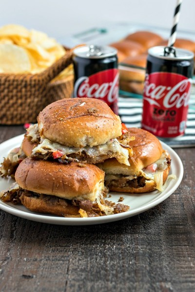 Philly Cheesesteak Sliders - A fun party food made by layering cooked beef, peppers, and onions with provolone cheese and baking in the oven between soft slider rolls just long enough to toast the tops and melt the cheese.