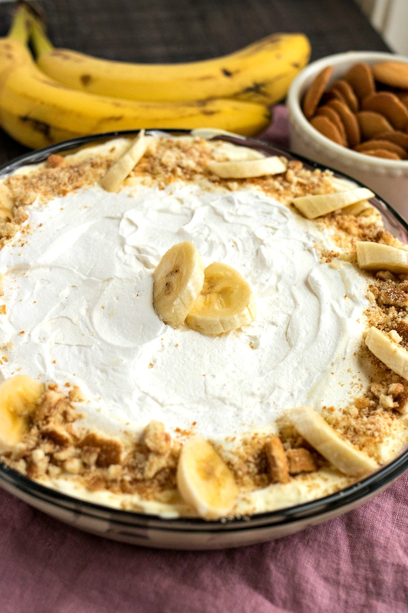 Pie dish of Banana Cream Pie Dip with a bowl of wafers and bananas in the back