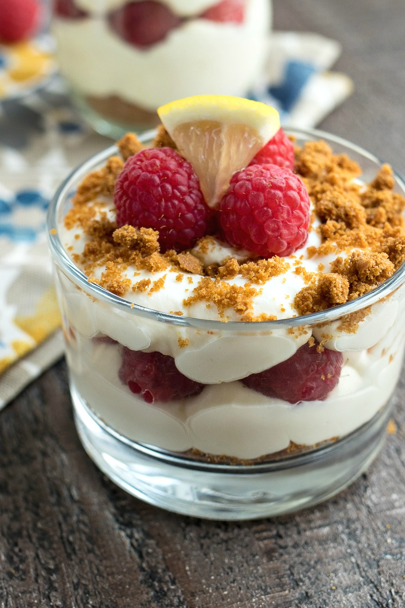 Dish of Lemon Raspberry Parfaits topped with raspberries and a lemon piece