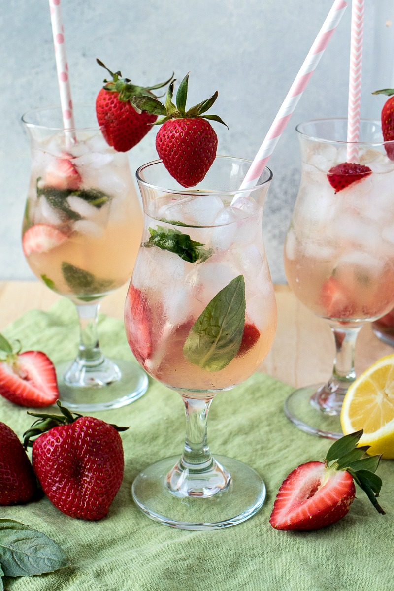 Glass of Strawberry Basil Vodka Punch with slices of strawberries and basil leaves