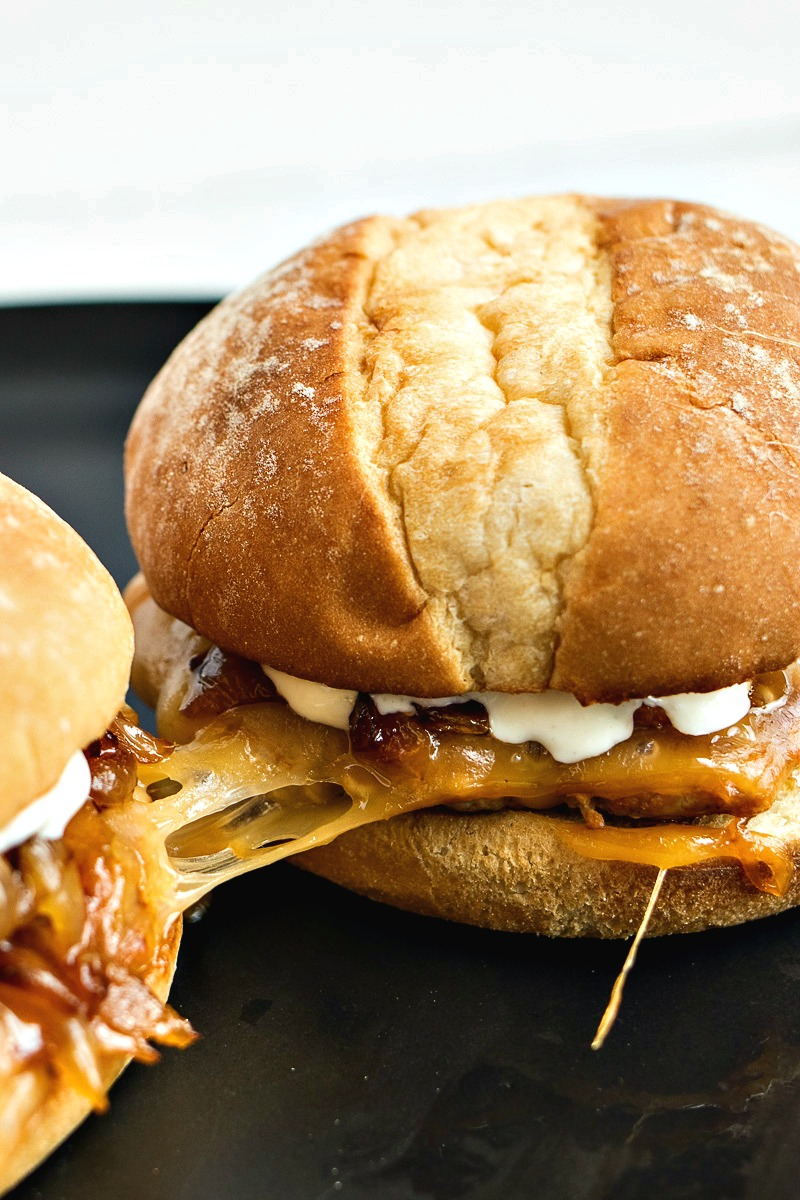 Pork Gouda Burgers with melted cheese stretching between the two burgers