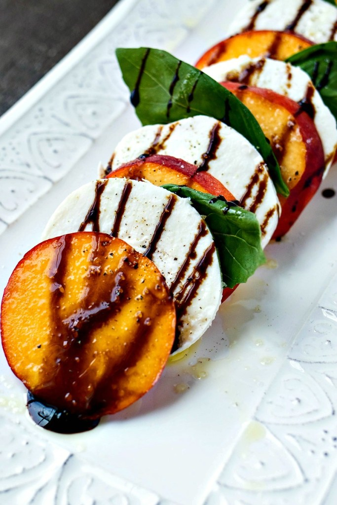 Tray of Peach Caprese Salad with balsamic vinegar drizzled across it