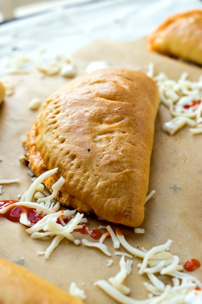 buffalo chicken pockets on a piece of parchment paper with buffalo sauce and cheese on it, shot from a side angle