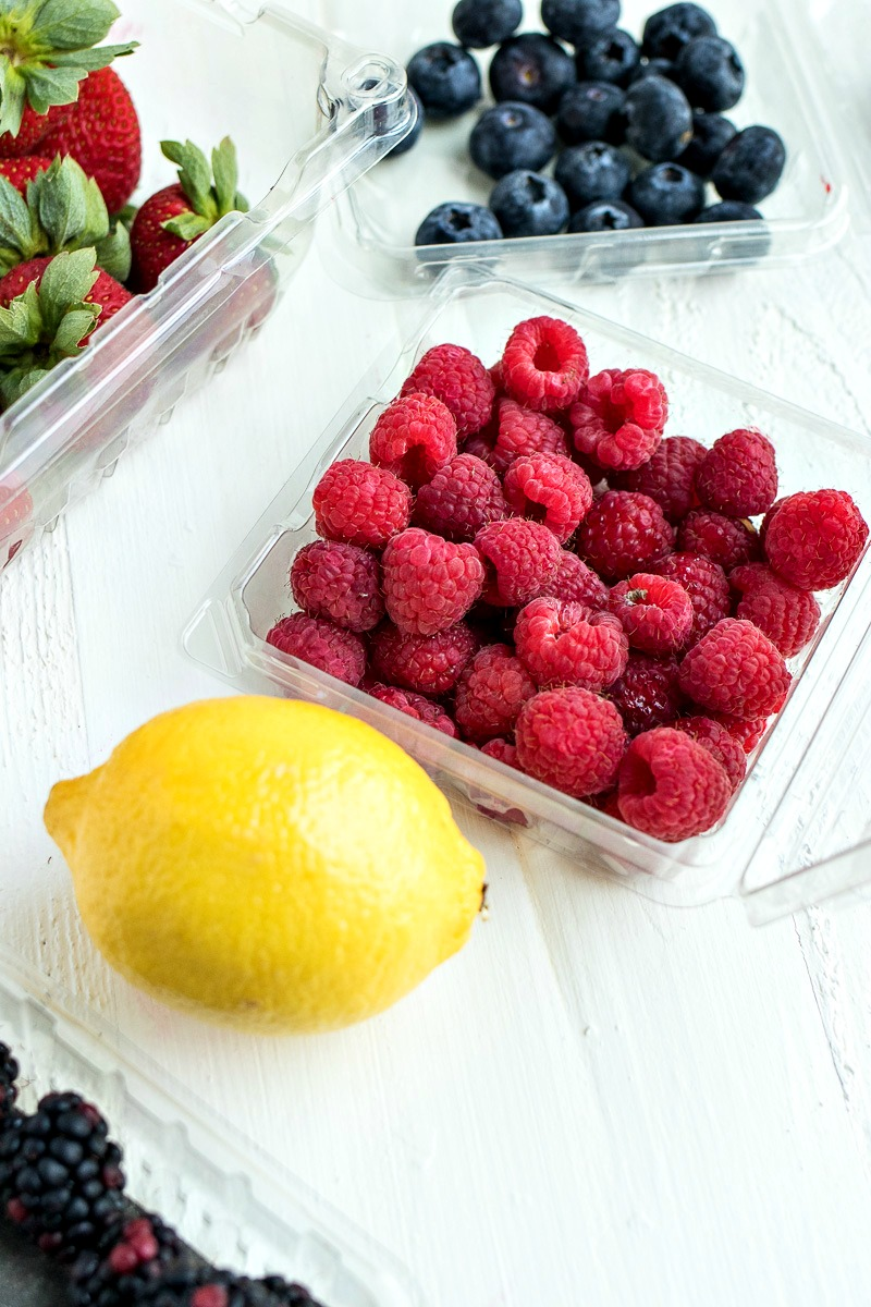 Plastic containers of berries next to a lemon
