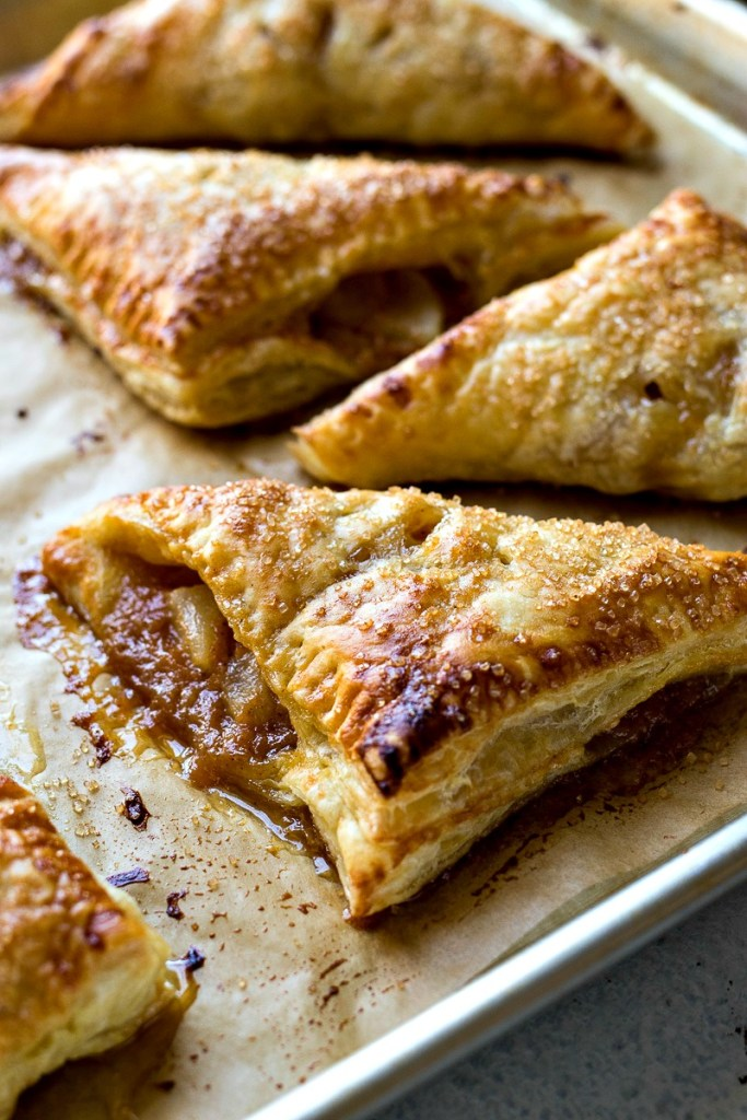 Butterscotch Pear Turnovers on a baking sheet with parchment paper, shot from a side angle