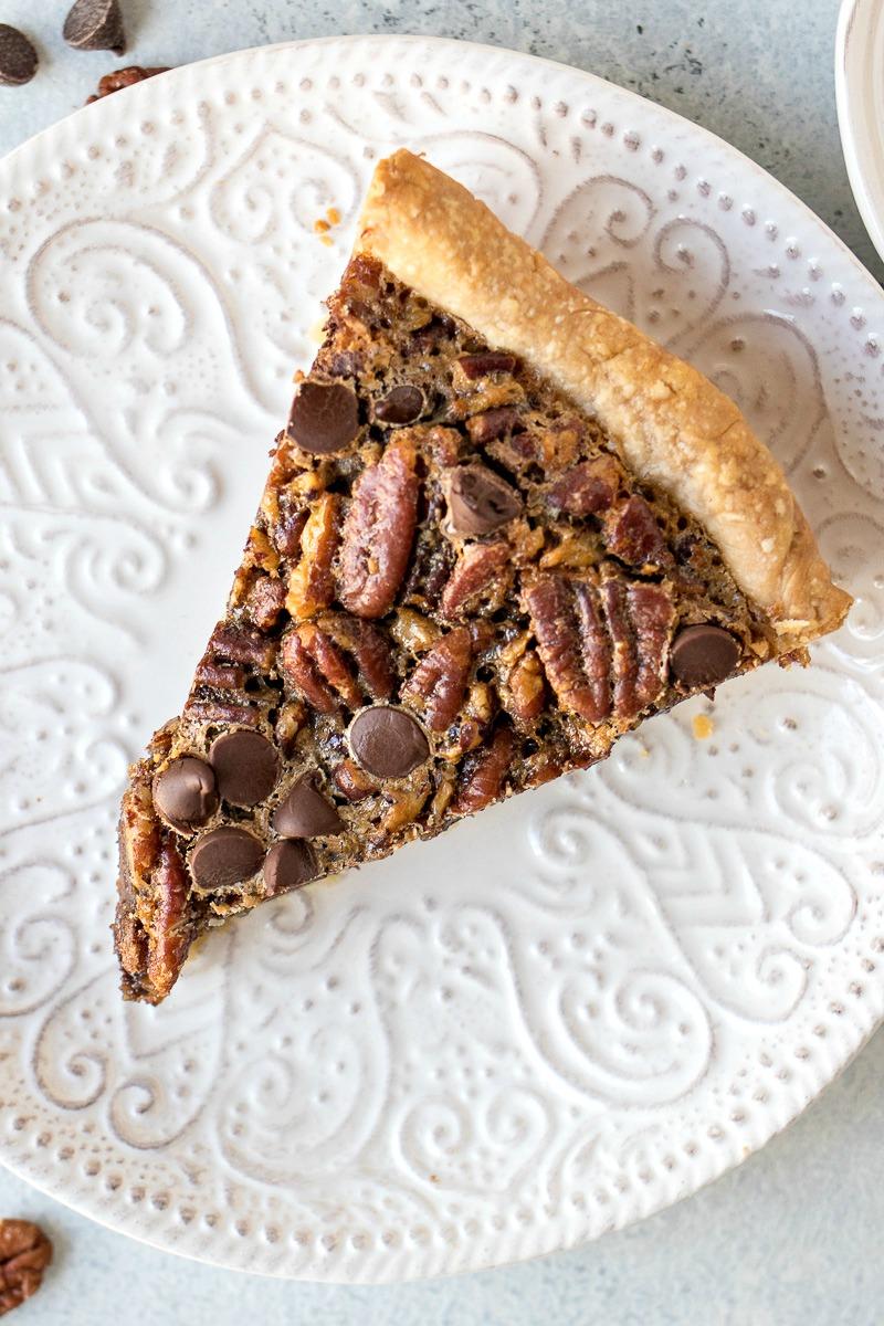 Slice of Chocolate Pecan Pie on a white pie dish