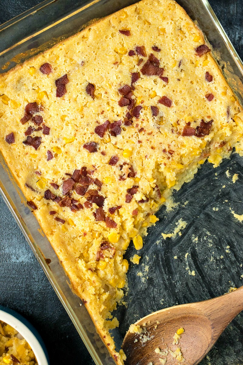 Scooping Bacon Corn Casserole with a wooden spoon
