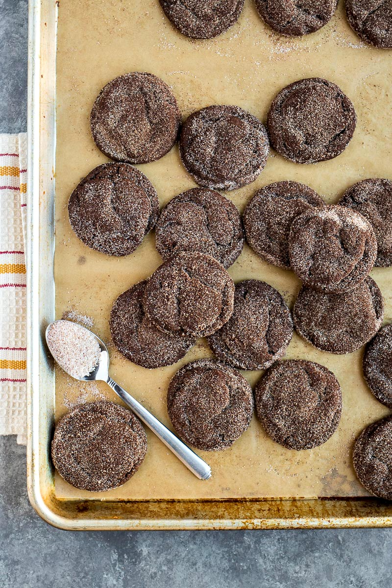 Cookie sheet of Chocolate Snickerdoodles with a spoon of cinnamon sugar