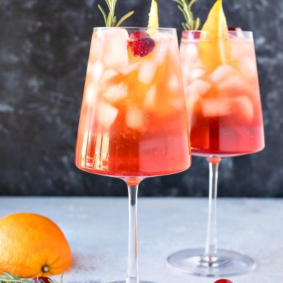 two stemmed glasses of Cranberry Orange Aperol Spritz with orange slices and rosemary sprigs with cramberries rosemary and half an orange on the table underneath, shot from the front