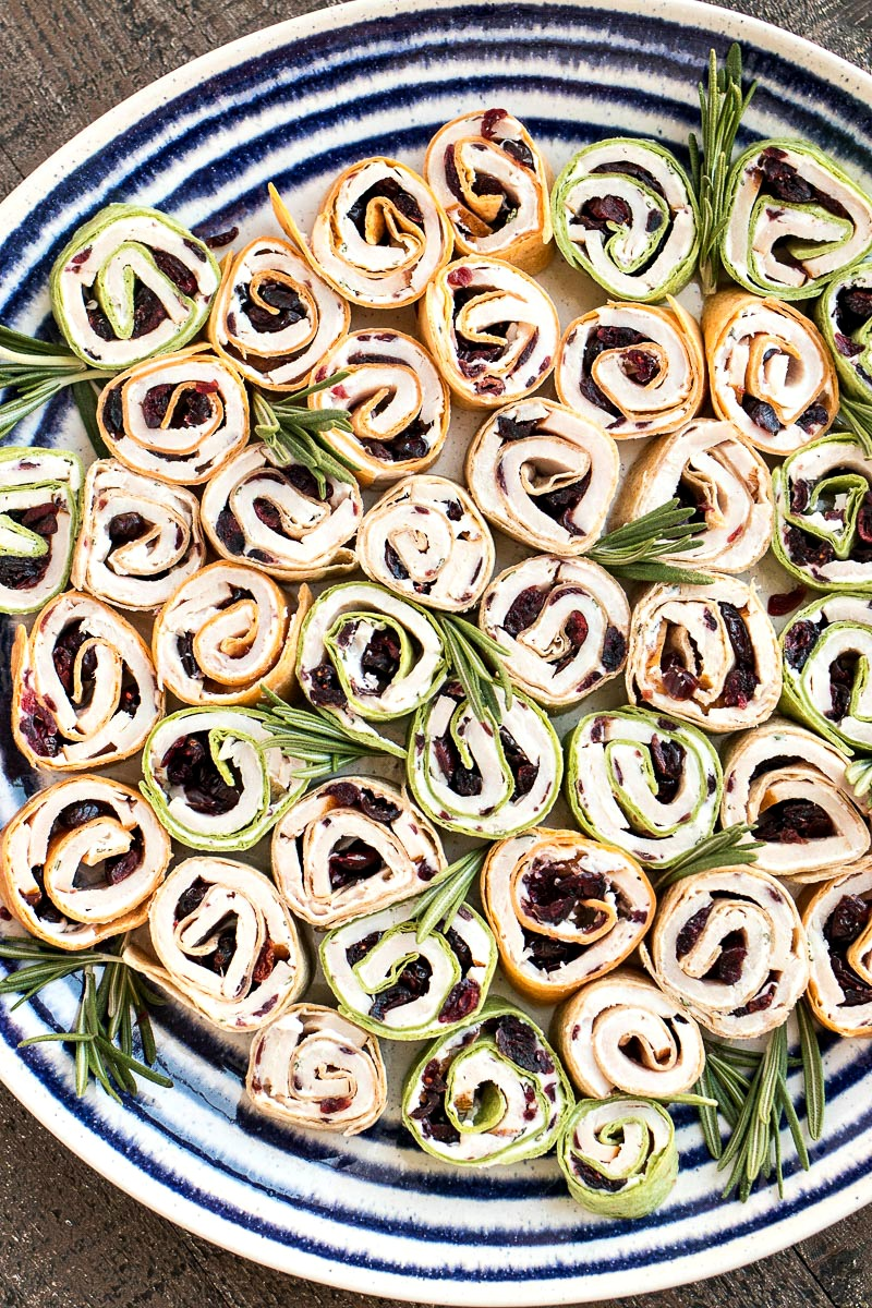 Turkey Cranberry Pinwheels on a plate with sprigs of rosemary