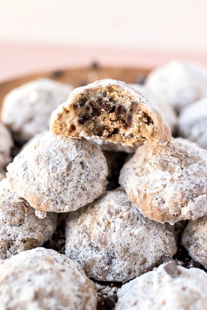 Stack of Cinnamon Chocolate Chip Snowballs with one cut in half to show the chocolate chips