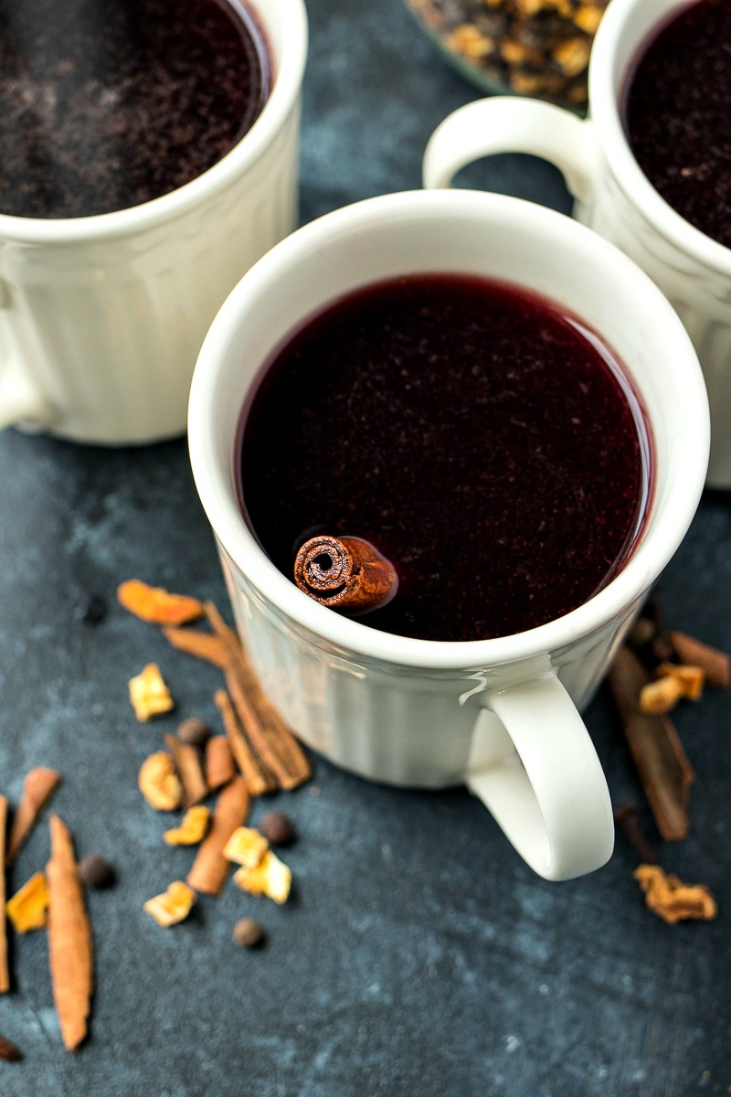Cup of Slow Cooker Mulled Wine with a cinnamon stick soaking in it