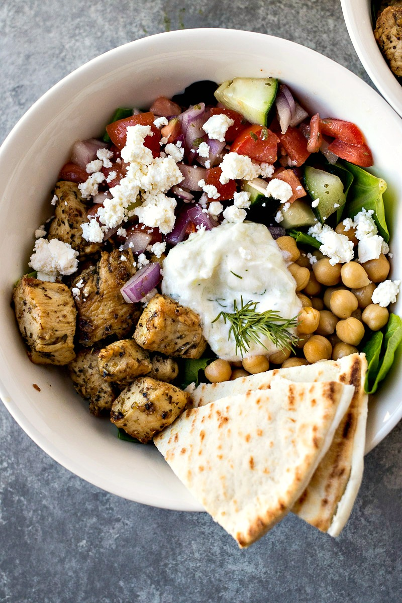 Bowl of Mixed greenstopped with Greek chicken, chickpeas, tomato cucumber salad, feta cheese, and tzatziki sauce with two pita slices