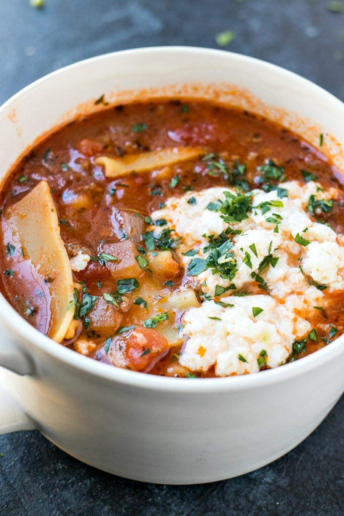 zoomed in show of a bowl of lasagna soup, shot from a side angle