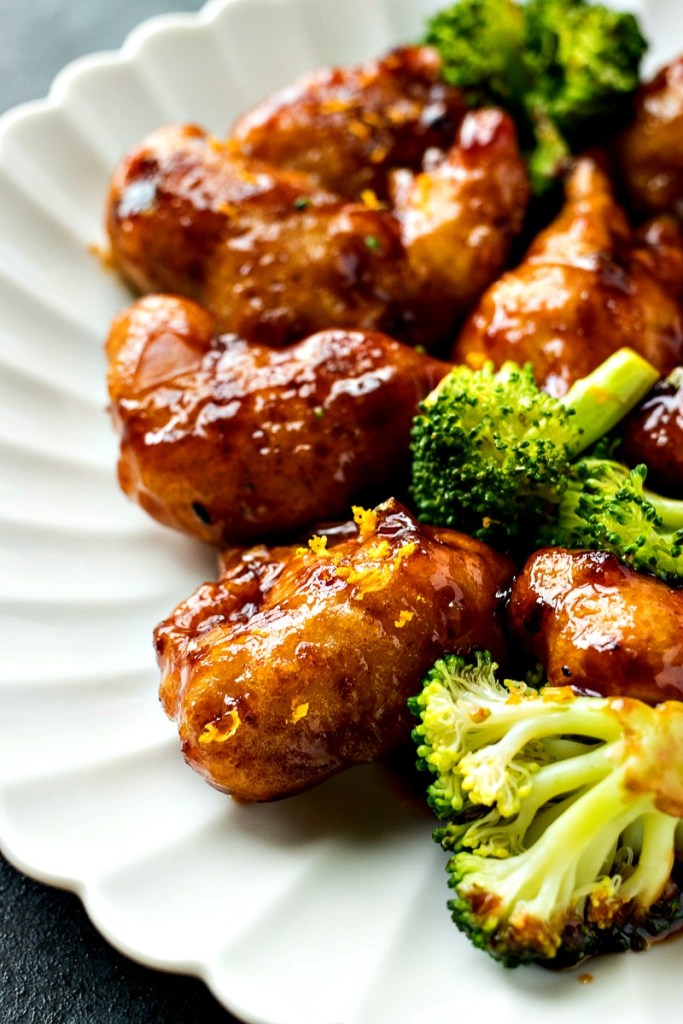 Plate of fired tempura chicken in an orange sauce with broccoli florets