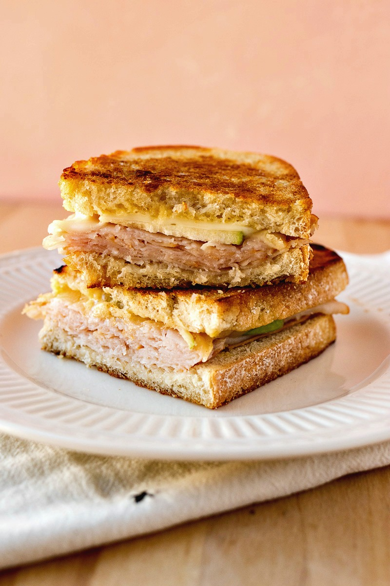 Plate of a Turkey Apple Melt cut in half and stacked on each other