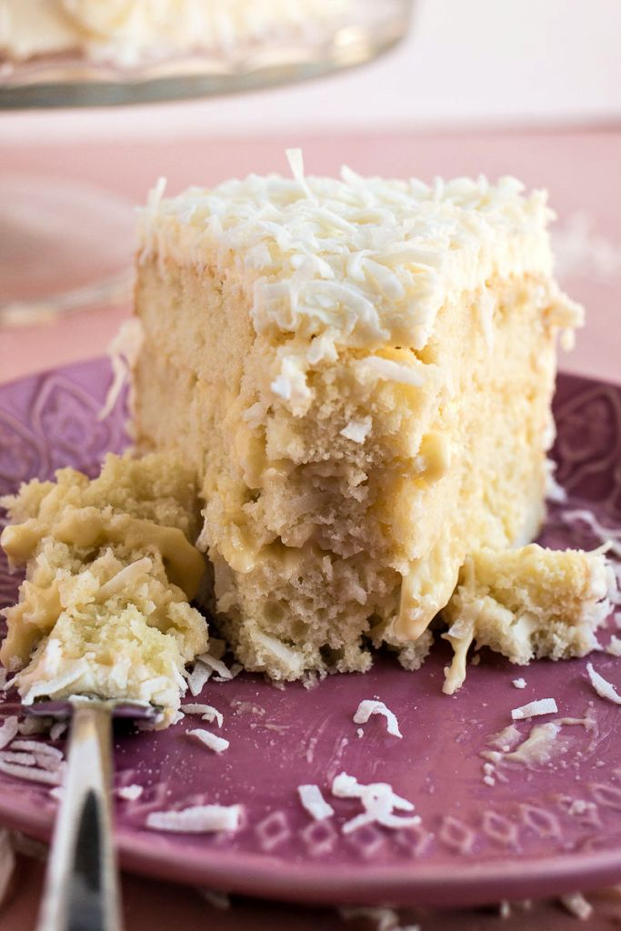 Closeup on a piece of Coconut Cream Cake showing the layers next to a forkful of cake