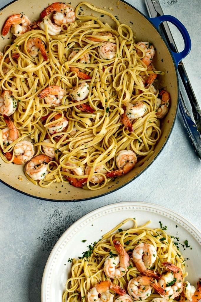 Pot of linguine and shrimp next to a plate of Shrimp Scampi with Linguine