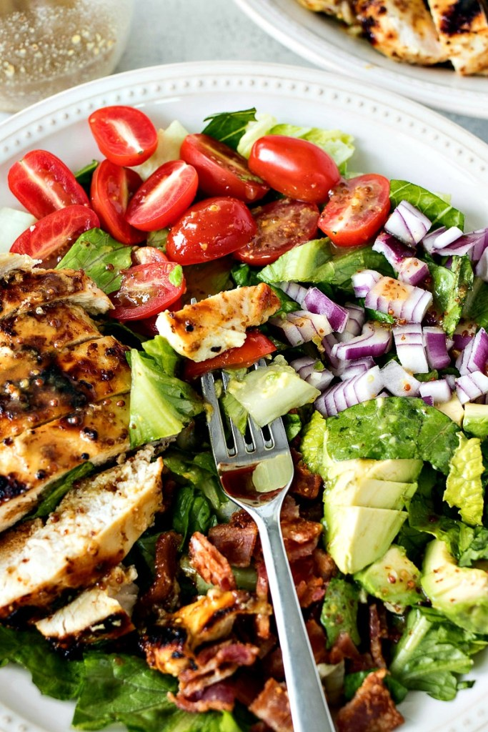 Forkful of chicken, tomato and lettuce above a plate of Honey Mustard Chopped Salad