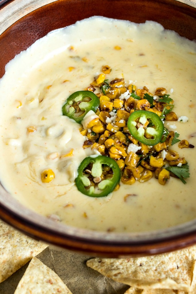 Bowl of Mexican Street Corn Queso with jalapeno slices and cheese topping in the middle